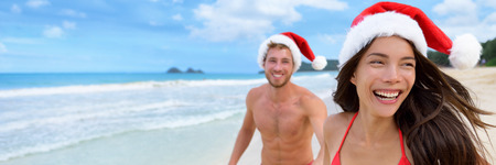 Happy Christmas holiday woman and man honeymoon couple laughing on beach vacation wearing santa claus hats carefree in freedom. Smiling Asian girl people lifestyle. Stock Photo