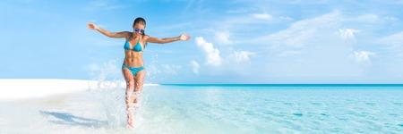 旅遊: 性感的比基尼身體女人在天堂熱帶海灘玩得開心玩打水自由的張開雙臂。美麗的身體女孩旅行假期。 copyspace的橫幅裁剪。