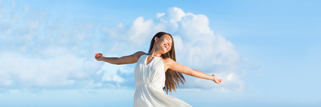 Serene free Asian woman with open arms in freedom or success on sky clouds panorama horizontal banner crop for copyspace. Serenity or bliss.