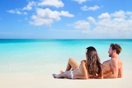 휴가 해변 바다 copyspace와 배경을보고 하얀 모래에 누워에 태양 선탠 편안한 행복 한 커플. 휴가 일광욕.