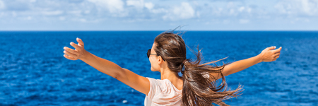Happy freedom woman with open arms looking at blue sea horizon outdoors. Carefree person living a free life. Panorama horizontal banner crop for success and bliss concept. Stock Photo