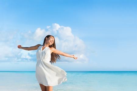 Vrijheid jonge vrouw met de armen gestrekt naar de hemel met blauwe oceaan landschap strand achtergrond kopie ruimte. Aziatisch meisje in witte jurk dansen zorgeloos in zonsondergang.