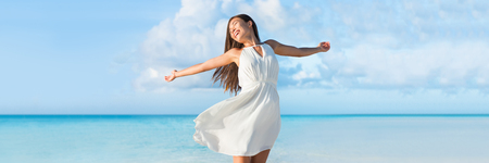 ocean background: Freedom young woman with arms up outstretched to the sky with blue ocean landscape beach background copy space. Banner panorama. Asian girl in white dress dancing carefree in sunset.