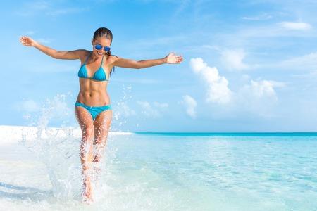 낙원 열대 해변 팔을 벌려 자유 튀는 물을 재생하는 재미에 장난 섹시 비키니 바디 여자. 럭셔리 여행 휴가에 아름 다운 몸에 맞는 소녀.