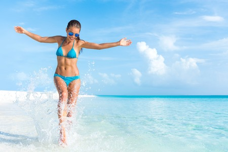 Sexy Bikini-Körper Frau spielerisch auf das Paradies tropischen Strand, der Spaß mit offenen Armen Spritzwasser in Freiheit zu spielen. Schöne Körper fit Mädchen auf Luxus-Reisen Urlaub. Standard-Bild