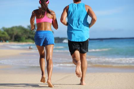 2 アスリート ランナー カップル実行一緒にビーチに。ジョギング離れて後ろから人熱帯旅行目的地の砂に裸足。下半身、足、足。