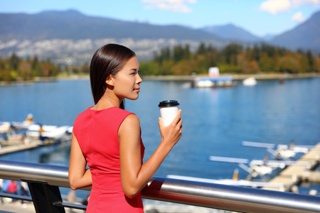 Asian businesswoman drinking coffee enjoying view of Vancouver harbor in city center. Business lifestyle. Stock Photo
