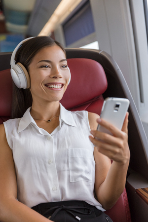 Modern people city lifestyle. Young urban woman using phone app and wireless headphones to listen to music or audiobooks online. Asian girl enjoying train travel in business class seat.