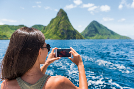 Cruise boat tourist taking mobile phone pictures of Deux pitons peaks, St-Lucia, Caribbean. The Gros and Petit Piton. Woman on shore excursion from ship in Castries, port of call.