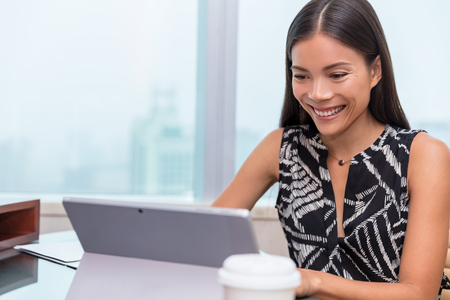 Asian woman smiling at laptop screen doing video chat conference online or working at office desk. Freelance work at home or customer service support.
