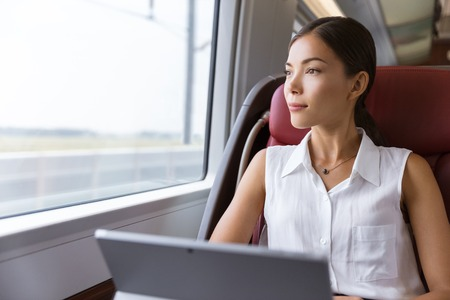 Asian woman traveling using laptop in train. Businesswoman pensive looking out the window while working on computer on travel commute to work.