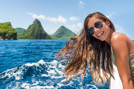 Happy tourist girl having fun on boat ride towards the deux gros pitons, famous attraction in St Lucia. World Heritage site. Young woman on shore excursion from cruise ship vacation travel.