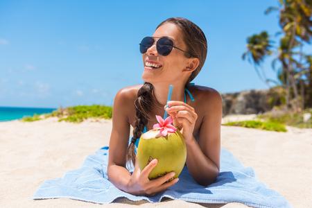 サングラスのビーチ夏バカンス楽しんでココナッツ水を飲む女性。熱帯旅行休日。ビキニのカジュアルな女の子が横になっているダウン自然健康ド