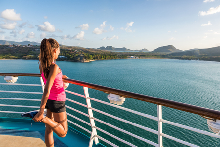 Fitness runner training stretching leg warm-up stretches before running on tracks of cruise ship boat. Woman enjoying view from deck of port of call Castries in St Lucia. Фото со стока