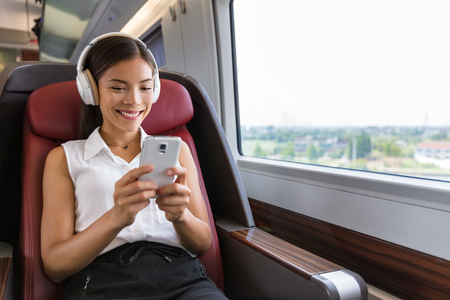 Modern people city lifestyle. Young urban woman using phone app and wireless headphones to listen to music or play video games online. Asian girl enjoying train travel in business class seat. Фото со стока