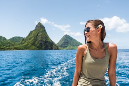 Happy woman cruising towards the deux gros pitons, popular tourist attraction in St Lucia. World Heritage site. Young traveler relaxing on shore excursion boat tour from cruise ship vacation travel. Stock Photo
