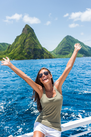 Happy freedom girl arms up having fun on excursion at Deux pitons, famous landmark of St Lucia. World Heritage site popular tourist attraction. Young carefree woman on summer holidays
