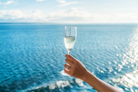 Champagne glass womans hand toasting on ocean background at luxury cruise ship during sunset. Travel vacation for honeymoon, lady holding flute wearing wedding ring. Stok Fotoğraf