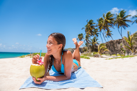 Happy girl lying down sun tanning on beach vacation. Asian woman relaxing sunbathing drinking fresh coconut water. Tropical travel destination, Suntan in summer holiday.
