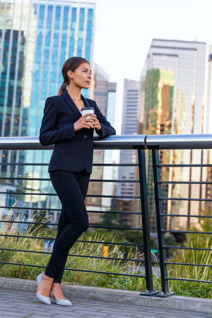 Businesswoman drinking coffee on break in business city center outside office buildings background. Asian woman pensive relaxing, young professional businesswoman in suit standing outdoors.