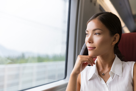Asian woman traveler contemplating outdoor view from window of train. Young lady on commute travel to work sitting in bus or train.