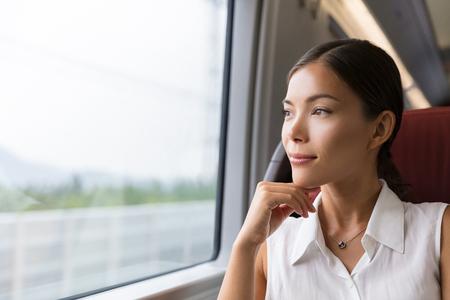 Aziatische vrouw reiziger overweegt openlucht uitzicht vanuit het raam van de trein. Jonge dame op pendel reis naar werk in de bus of trein zitten.
