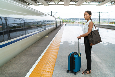 railway transport: Asian traveler woman waiting for travel on railway platform. Businesswoman standing with luggages at central station, train on time or delayed. Departure transport concept. Stock Photo