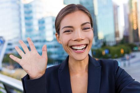 Mujer de negocios que toma la foto usando autofoto aplicación de teléfono inteligente en el smartphone para los medios de comunicación social. Joven empresaria utilizando el teléfono inteligente sonriendo feliz que lleva la chaqueta del juego al aire libre. profesional femenino urbano. Foto de archivo
