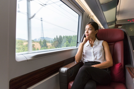 Woman relaxing enjoying view during morning commute. Business class seat in train. Asian businesswoman pensive looking out the window in travel transport.
