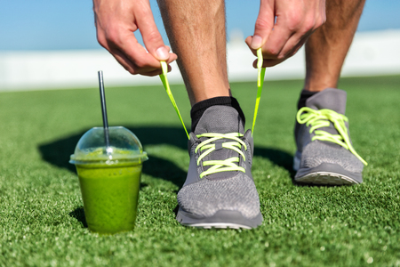 Green smoothie fitness man lacing running shoes, Athlete runner with green vegetable detox juice getting ready for morning run tying running shoe laces on grass. Fitness and healthy lifestyle concept. Stock Photo