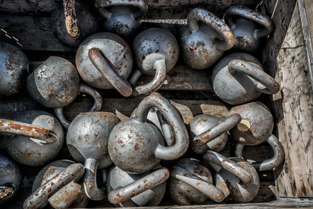 Many kettlebells weights background at outdoor gym. Texture of stell free weights for weightlifting lying on the floor at fitness center for cross training.