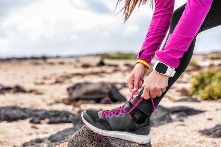 Fitness smartwatch vrouwloper lacing lopende schoenen op het strand, Atleet meisje klaar voor hardloop trainen koppelen lopende schoen veters buiten dragen horloge versnelling. Gezond levensstijl concept.