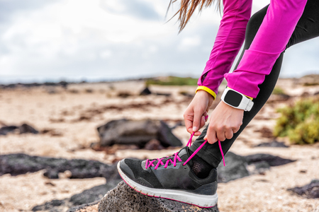 Fitness smartwatch woman runner lacing running shoes on beach, Athlete girl getting ready for run workout tying running shoe laces outside wearing watch gear. Healthy lifestyle concept. Stock Photo