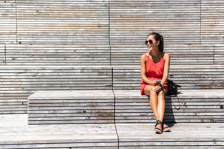 Woman in New York relaxing on bench on High Line relaxing laughing happy holding mobile phone using smartphone app. Summer travel tourist sitting resting during visit of popular touristic attraction.