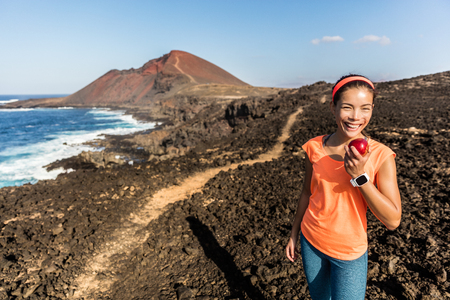 Happy hiker hiking on mountain trail path taking a break eating a healthy snack - apple fruit. Fitness woman runner on trail running training enjoying organic food in mountains landscape. Stock Photo