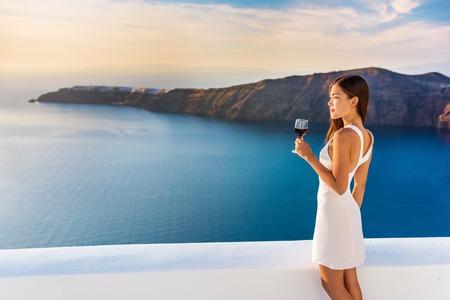 高級ホテルのテラス。ヨーロッパ先夏休み。アジアの女性は、イア、サントリーニ島、ギリシャの地中海の景色を楽しみながらリラックスした赤ワ
