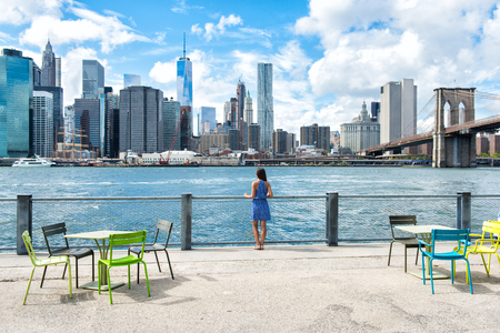 New York city skyline waterfront lifestyle - woman enjoying view. American people walking enjoying view of Manhattan over the Hudson river from the Brooklyn side. NYC cityscape with a boardwalk.