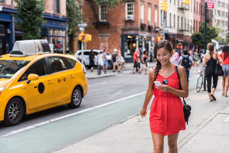 Woman walking in new york city using phone app for taxi ride hailing service or playing online game while commuting from work. Asian girl tourist searching for map directions on smartphone.