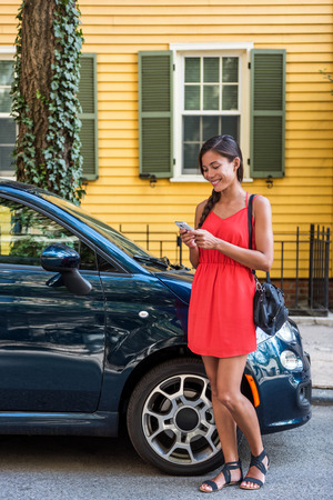 Asian woman using mobile phone app for car sharing service or city traffic information in front of her house. New car owner using phone to check status, control her new car. Smartphone taxi concept. Banco de Imagens