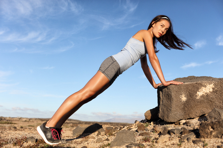 Strength training fitness woman working out core with angled pushups or planking on rock. Asian athlete exercising with bodyweight exercises for toned body. Workout in summer desert landscape. Stock Photo