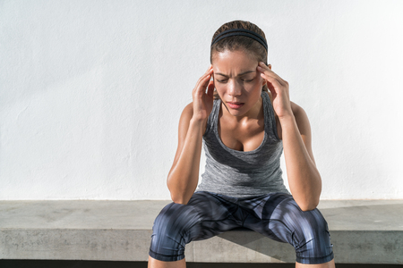 Athlete fitness running woman with headache migraine pain during cardio workout run. Asian athlete with health problem feeling exhausted during difficult strength training exercise at gym. Stock Photo