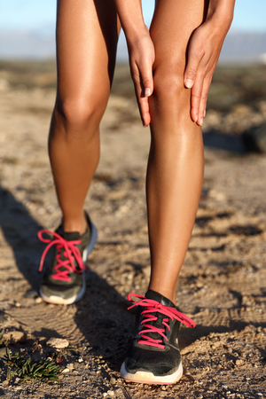 Runner woman gripping painful hurt knee pain. Athlete woman running outside with body injury. Closeup of strained joint on run in summer outdoors nature. Fitness leg accident during cardio workout.