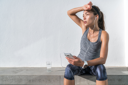 Tired fitness woman sweating taking a break listening to music on phone after difficult training. Exhausted Asian runner dehydrated feeling exhaustion and dehydration from working out at gym. Banque d'images
