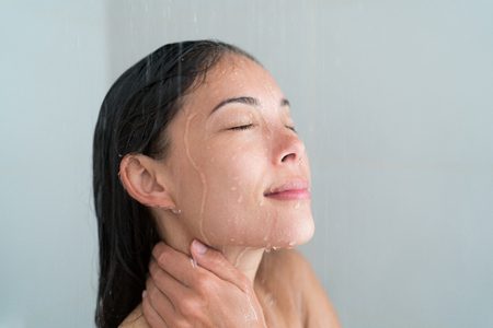 Shower woman showering relaxing under water massaging neck in hot shower. Asian female adult face enjoying spa relaxation time relaxing meditating in warm bath cleaning face and body at home.