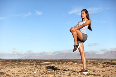 Standing Gluteus maximus leg stretches. Fitness woman doing stretch exercises workout stretching glutes muscles and hamstring as warm-up for cardio exercise. Trail running in summer outdoor nature. Stock Photo