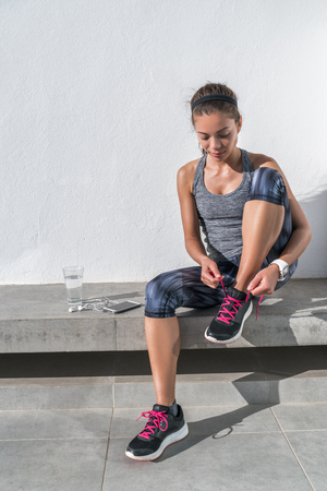 Active Asian woman getting ready for run tying running shoes on outdoor bench with smartphone, earphones earbuds and a glass of water. Athlete sporty runner in activewear living a healthy lifestyle.