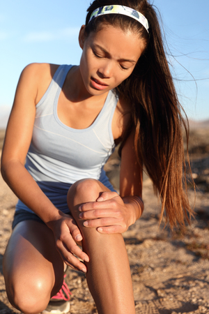 sprained joint: Runner woman gripping painful hurt knee pain. Athlete woman running outside with body injury. Closeup of strained joint on run in summer outdoors nature. Fitness leg accident during cardio workout.
