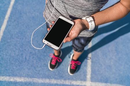 Runner meisje bedrijf smartphone met behulp van touchscreen voor het kiezen van muziek of sms'en sms op app voordat u op het goede spoor. Vrouwelijke atleet vrouw voeten en benen close-up met de SmartWatch en met de hand aanraken display.