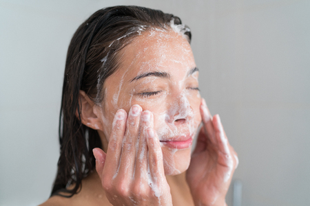 Skincare woman washing face in shower foaming facewash soap scrub on skin. Asian female adult cleaning body showering in hot water at home on in hotel as morning routine. Enjoying relaxing time. Stock Photo - 77776245