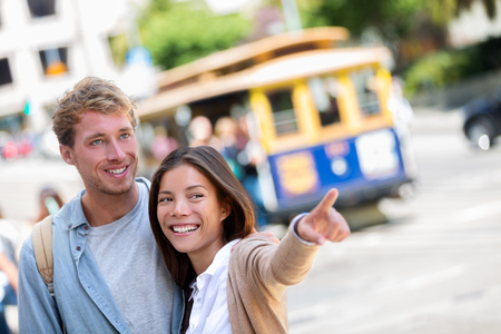 San Francisco city travel couple tourists people lifestyle. Young interracial students on city street, woman pointing, cable car railway system in the background, popular attraction in San Francisco. Stock Photo